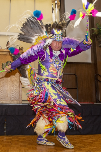 A traditionally-dressed Native American performer performs