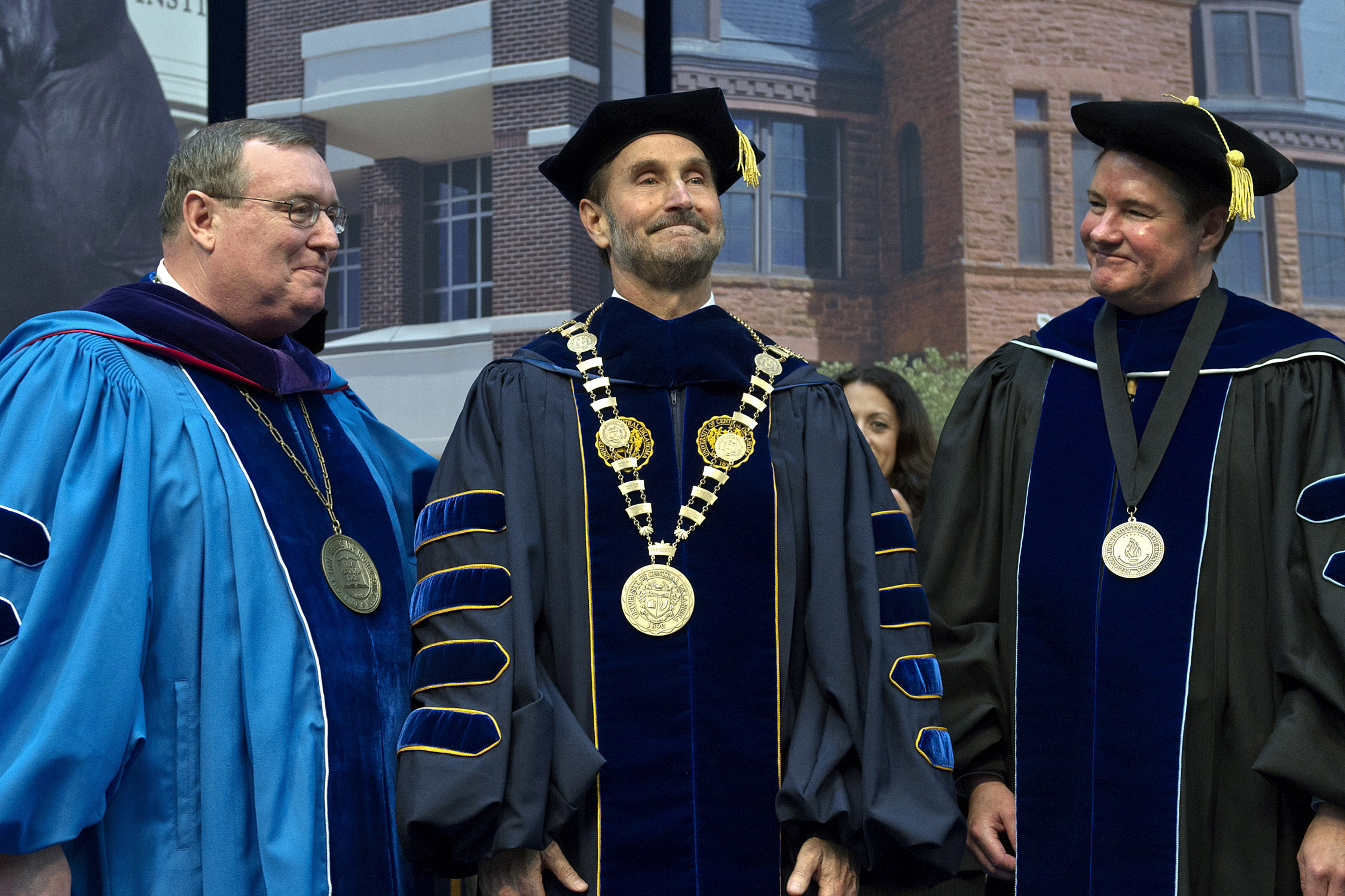 Oklahoma State Regents for Higher Education Chancellor Glen Johnson, J.D. (left), and Regional University System of Oklahoma Secretary Richard C. Ogden, J.D. (right) smile after placing the University of Central Oklahoma's medallion, a symbol of the presidential office and its authority, upon Don Betz, Ph.D. (center), during his inauguration Friday as the university's 20th president.