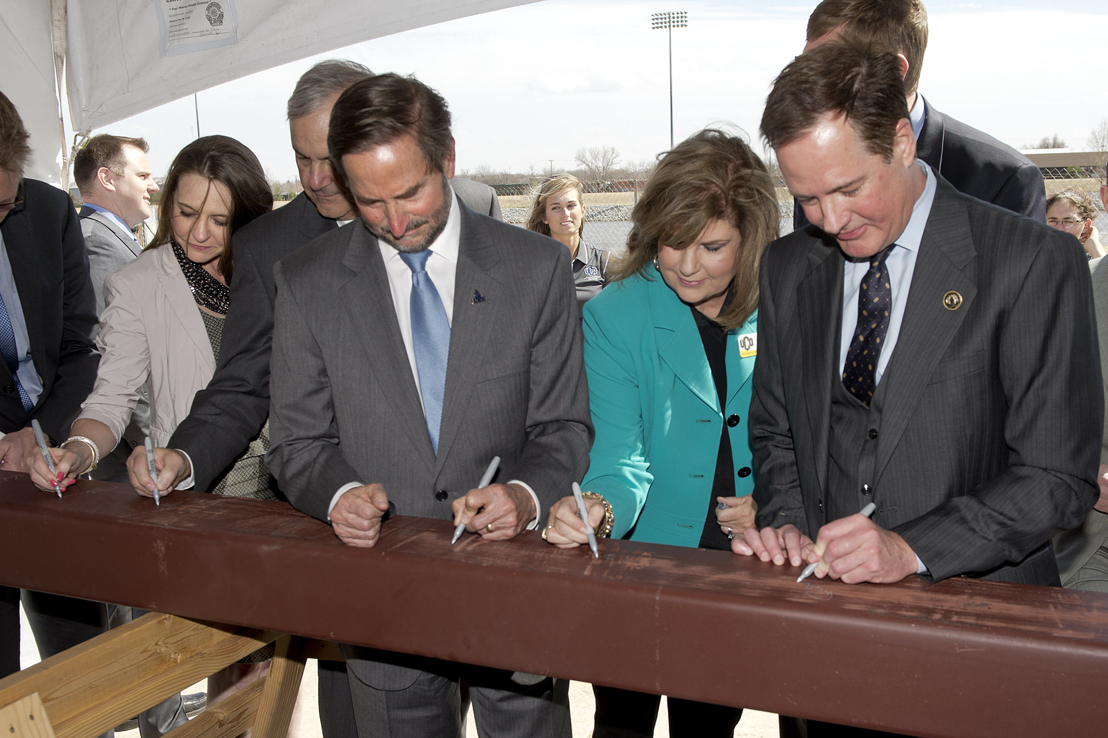 UCO President Don Betz, First Lady Suzanne Betz and RUSO Regent Richard Ogden sign a beam that will be used in the construction of the CHK|Central Boathouse during a ceremony to celebrate the construction of the boathouse on Thursday, March 27, at the Oklahoma River.