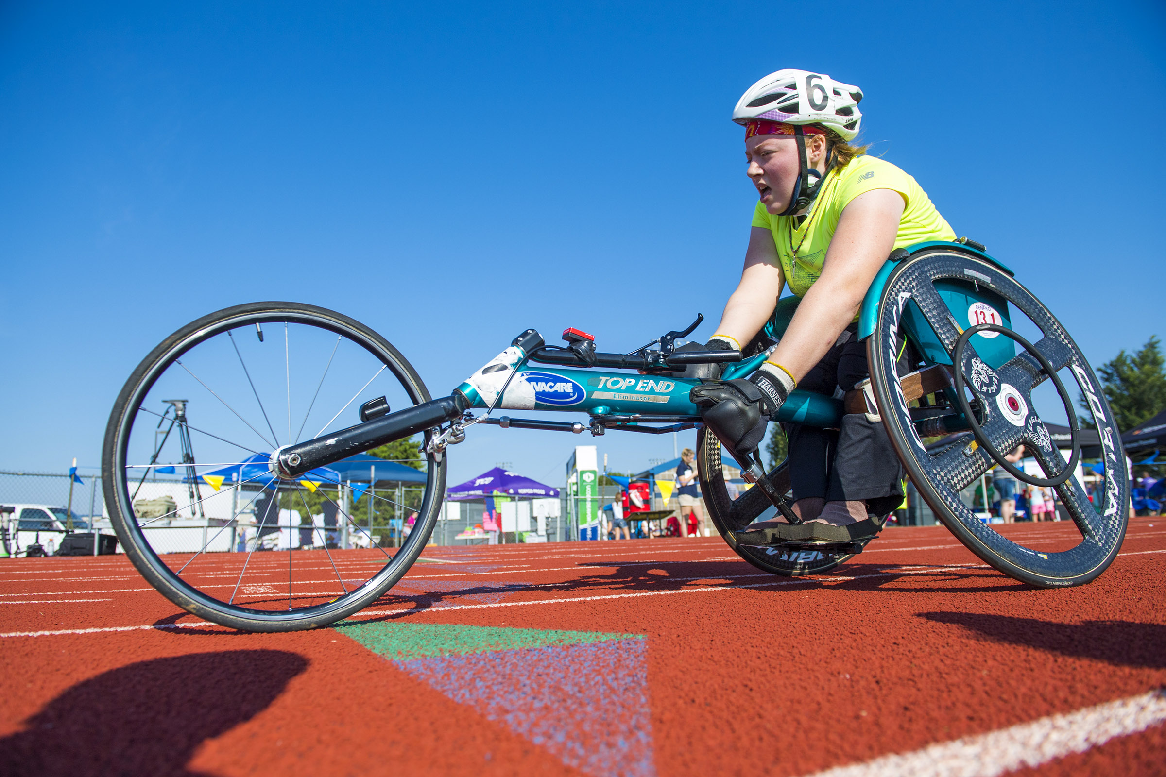 A disabled, female athlete rides a cycle along a track.