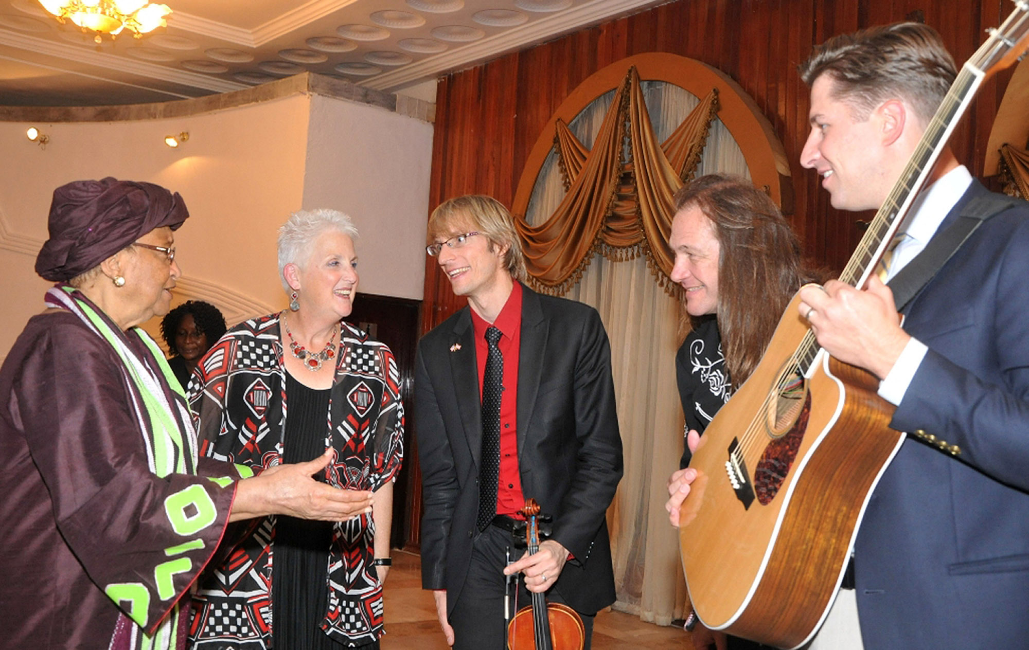 President of Liberia Ellen Johnson Sirleaf (far left) and U.S. Ambassador to Liberia Deborah Malac (second from left) with Kyle Dillingham (third from left), Brent Saulsbury (fourth from the left) and 2014 Oklahoma's Teacher of the Year, Peter Markes (far right), greet one another during Horseshoe Road's recent American Music Abroad tour of Liberia. Members of the band will perform and highlight the tour at the UCO International House Sept. 4.