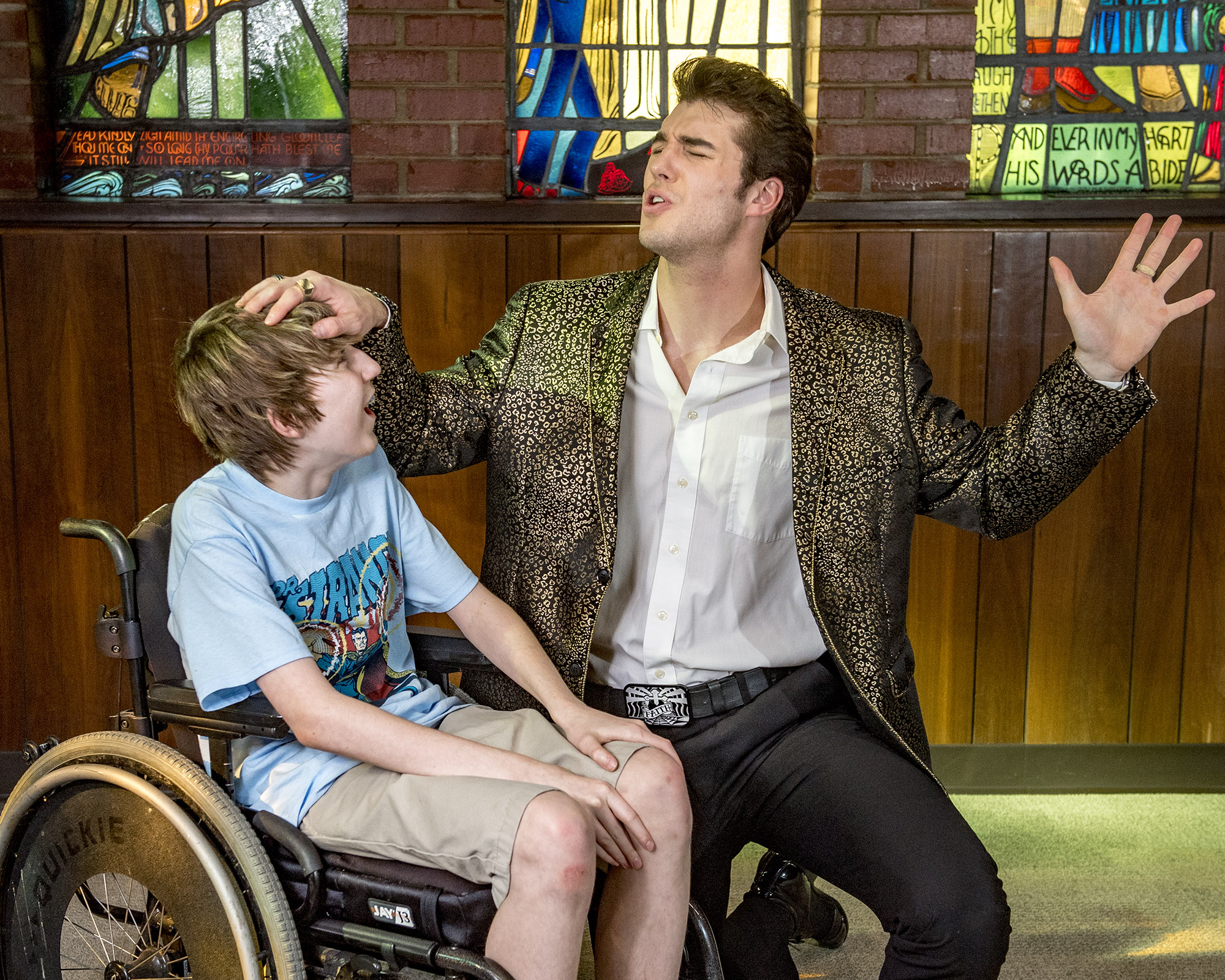 Young boy in wheelchair, left, looks up at singing man, on the right.