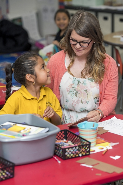 A young student looks up and to the right, to her teacher, Megan Byrum.