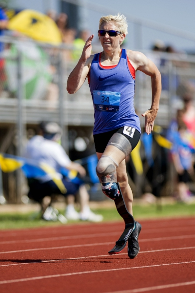 A female runner with a prosthetic leg runs along a track.