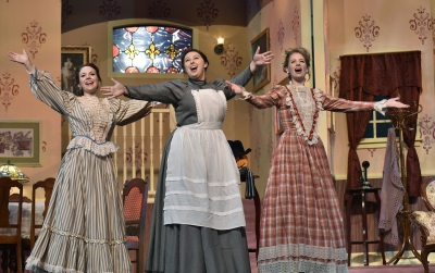 Three women in dresses sing on stage during a musical theatre production