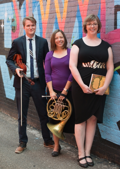 Three people stand in a group; a man holds his violin, a woman holds a horn instrument, and another woman holds a book of sheet music and compositions.