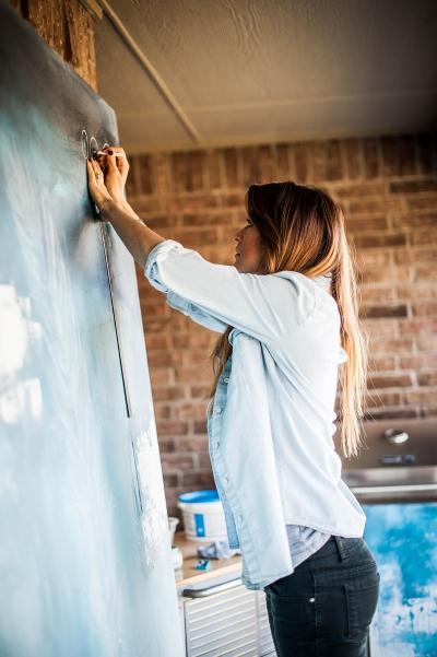 A woman paints on a large canvas