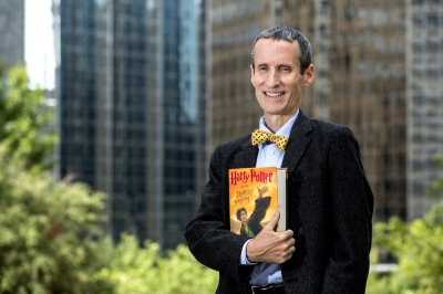"""A man, John Granger, stands holding the copy of the book """"Harry Potter and the Deathly Hallows,"""" while standing in front of a background of city buildings in downtown Oklahoma City."""