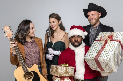 Female with a guitar, female singing, and male with a cowboy hat surround another male dressed as Santa holding presents.