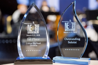 "Two awards sit side-by-side. On the left, the award reads, ""Monterey Jazz Festival Presents Next Generation Jazz Festival, March 9-11, 2018, 1st Place, College Big Band Division,"" and, on the right, the adjacent award reads, ""Monterey Jazz Festival Presents Next Generation Jazz Festival, March 9-11, 2018, Outstanding Soloist."""