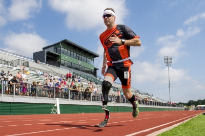 A man with a prosthetic leg runs on a track during a track and field event.