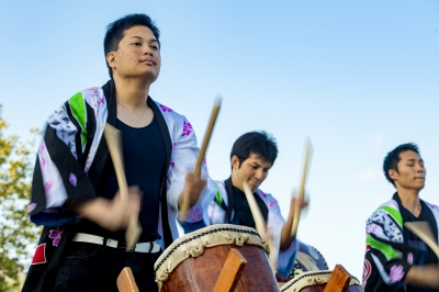 Three male students play on drums during an Asian Moon Festival performance.