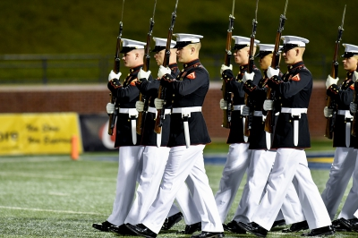 A group of U.S. Marines performs a traditional silent drill ceremony on Wantland Stadium's field.