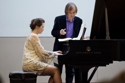 Man teaching a student how to play the piano