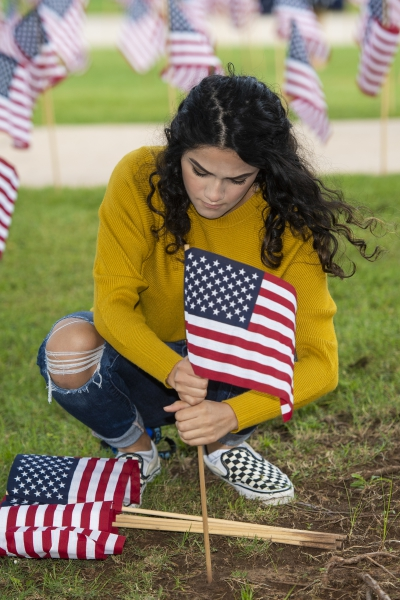 A woman places a small American flag in the ground